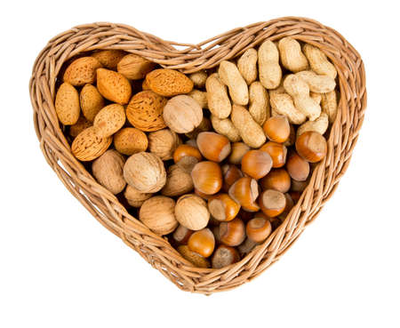 collection of shelled nuts in a heart-shaped basket isolated on white  photo