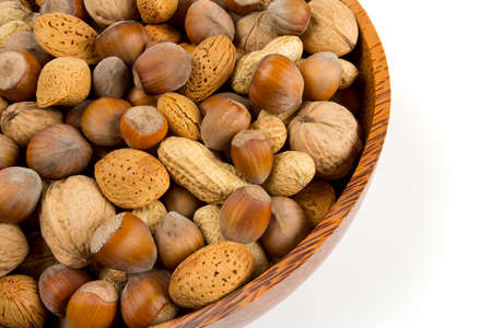 collection of shelled nuts in a wooden bowl isolated on white photo