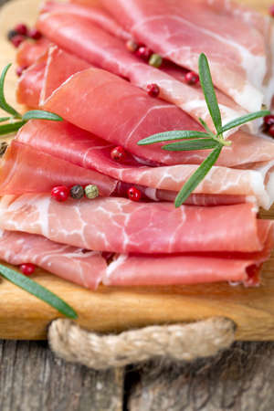 sliced prosciutto on a wooden table Stock Photo - 24027509