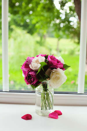 white and violet roses on window sill photo