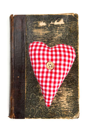 heart-shaped decoration on old book isolated on white photo