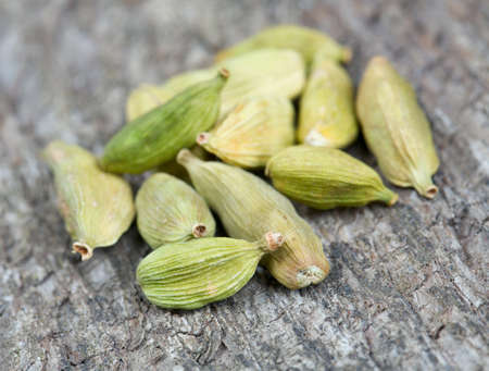 cardamom pods on wooden surface