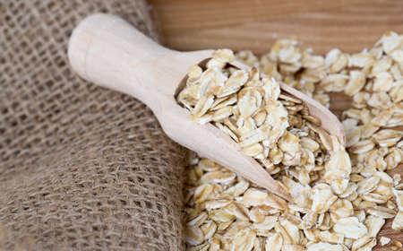 oat flakes in a scoop on wooden surface photo