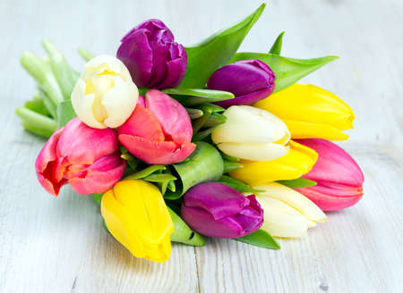colorful tulips on wooden table photo