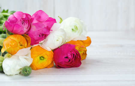 bouquet of white, pink and orange buttercups on wooden table photo