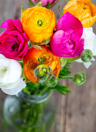 bouquet of ranunculus flowers on wooden surface photo