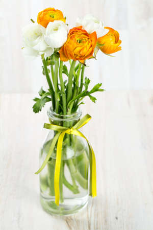 bouquet of white and orange buttercups on wooden table photo