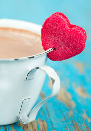 hot chocolate and heart-shaped marshmallow on wooden surface photo