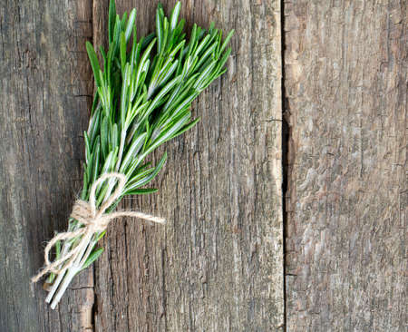 bunch of rosemary on wooden surface photo