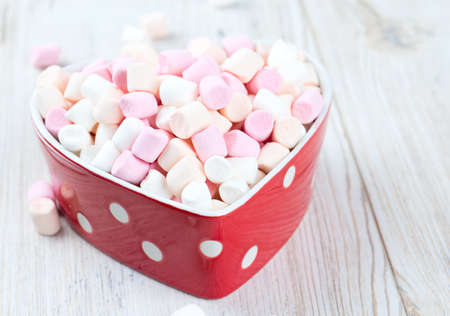 marshmallows in heart shape bowl on a wooden table photo