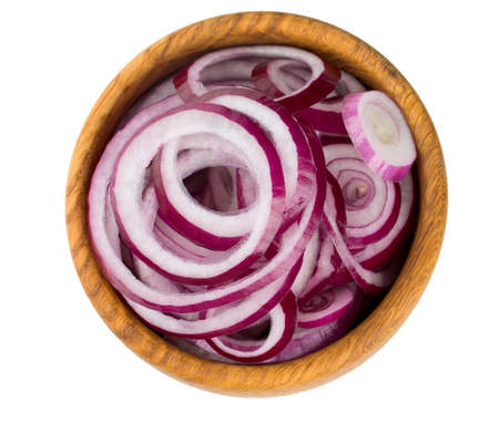 red onion slices in a wooden bowl isolated on white photo