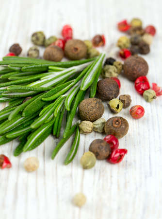 rosemary and peppercorns on wooden table photo