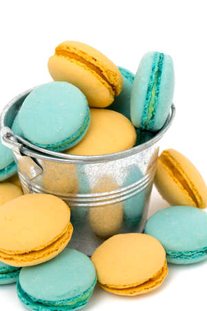 blue and yellow macarons in a bucket over white photo