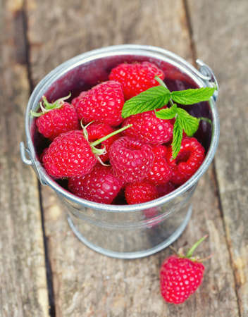 raspberries in a bucket on wooden surface photo