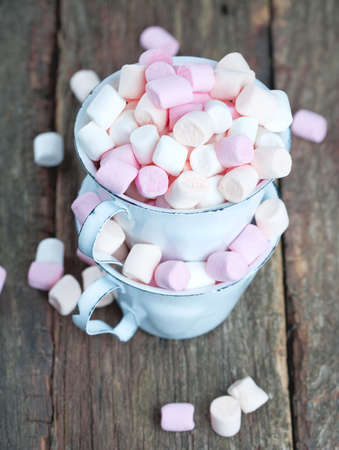 marshmallows in metallic cups on wooden table photo
