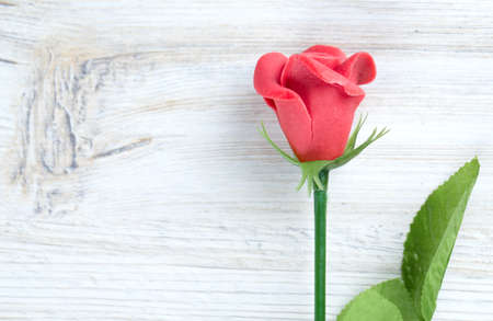 marzipan rose on wooden surface photo