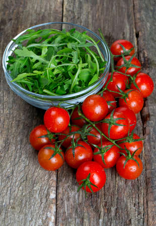 fresh rucola and cherry tomatoes on wooden surface photo