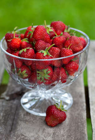 strawberries in a beautiful glass dish on wooden table photo