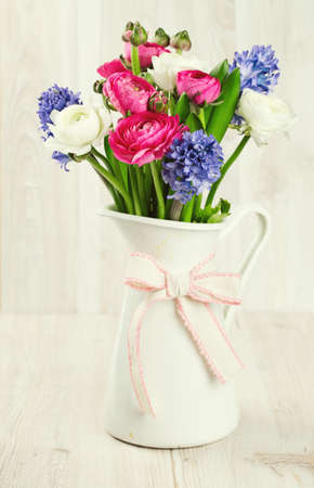 ranunculus and hyacinth flowers in a pitcher on wooden surface photo