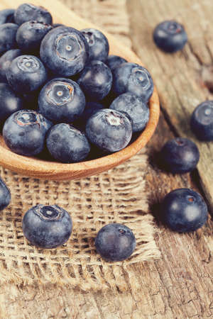 fresh blueberries in a wooden spoon over wooden table photo