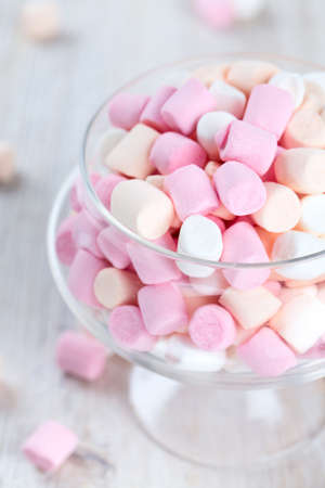 marshmallows in beautiful glass dish on a wooden table photo