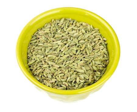 fennel seeds in a green bowl isolated on white background photo