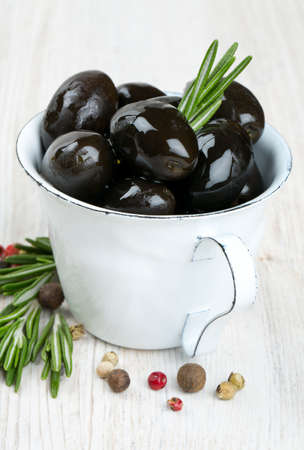 black olives in a metallic cup on wooden surface photo