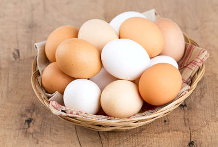 farm eggs in a basket on wooden table photo