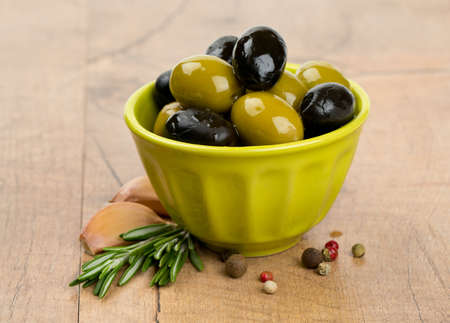 green and black olives in a green oil photo