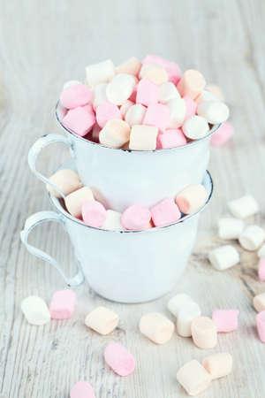 marshmallows in metallic cups on wooden table photo