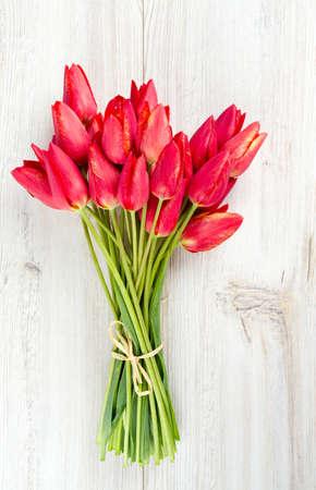 Strauß roter Tulpen auf Holzoberfläche Standard-Bild