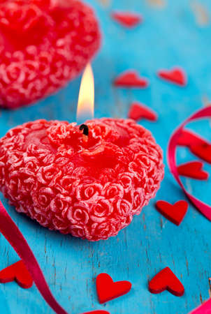 red candle, hearts and ribbons on a blue wooden surface photo