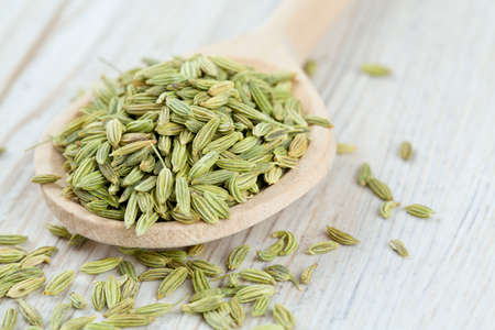 fennel seed: fennel seed in a wooden spoon on table