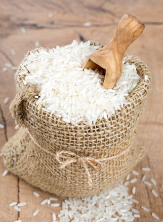 rice in a burlap bag on wooden surface photo