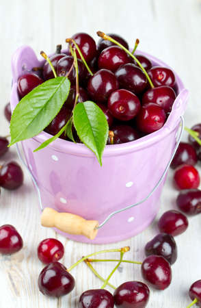cherries in a bucket on wooden table photo