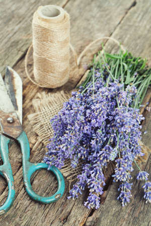 fresh lavender, scissors and thread on wooden surface photo