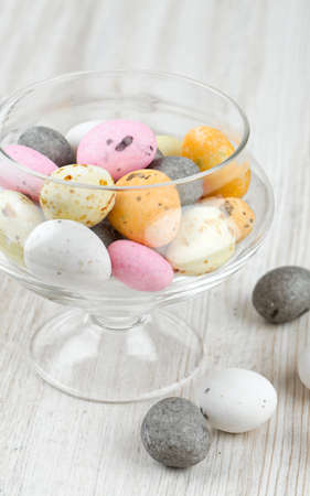 candies in a glass dish on wooden table Stock Photo