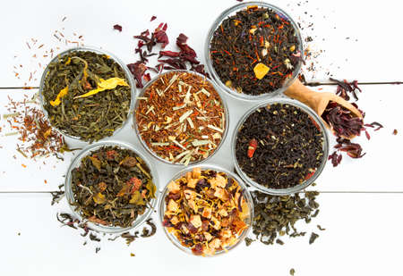 assortment of dry tea in glass bowls on wooden surface photo