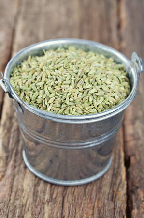 fennel seeds in a bucket on wooden surface photo