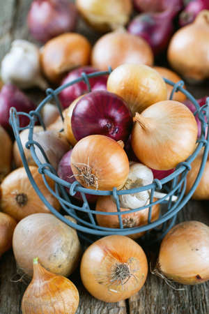pealing: red and yellow onion in an iron basket on wooden surface
