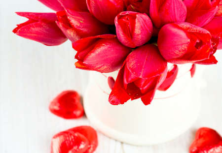 tulips in vase on wooden surface and chocolate hearts photo