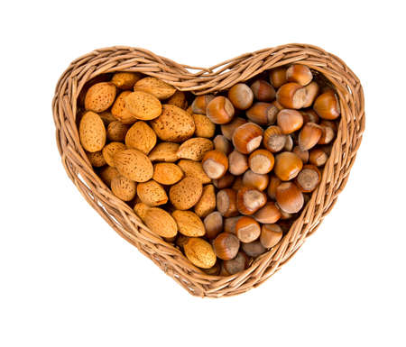 whole pecans: collection of shelled nuts in a heart-shaped basket isolated on white