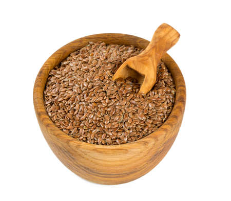 flax seed in a wooden bowl isolated on white