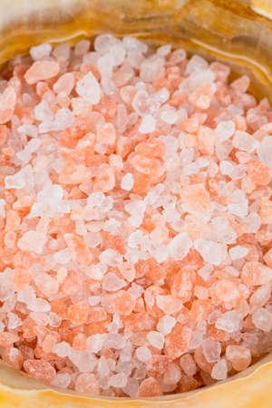 himalayan salt: pink himalayan salt in a mortar on wooden surface Stock Photo