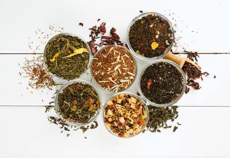 assortiment van droge thee in glazen kommen op houten oppervlak Stockfoto