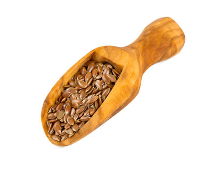flax seed in a wooden scoop isolated on white photo
