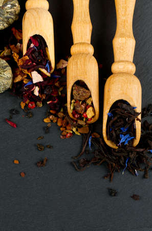 assortment of tea in scoops on black stone background photo