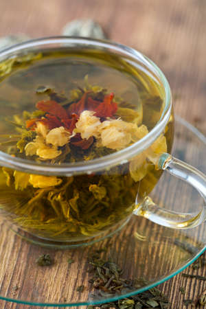 exotic green tea with flowers in glass cup photo