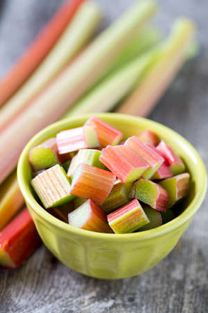 freshly cut pieces of rhubarb on wooden surface photo