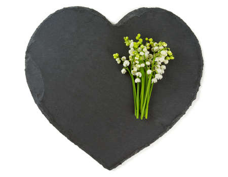 muguet: lilly of the valley on black stone heart Stock Photo